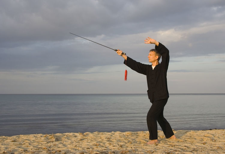 Mature man practicing tai chi with sword at beach against cloudy sky