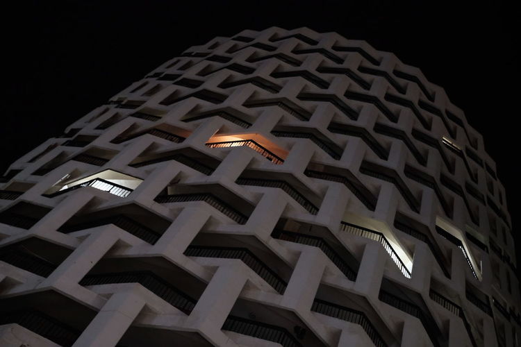 Low angle view of illuminated lights against building at night