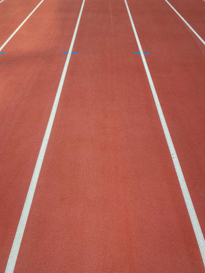Lane on a red athletics track with white lines and blue marks