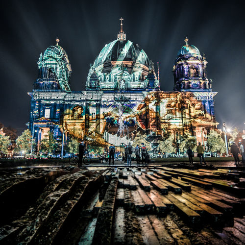 People in front of illuminated berlin cathedral at night