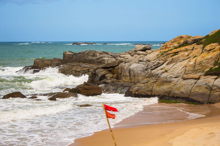 Beach Beauty In Nature Clear Sky Cliff Day Flag Horizon Over Water Mar Nature No People Outdoors Patriotism Pedra Perigo Rock - Object Rock Formation Scenics Sea Sky Tranquil Scene Tranquility Travel Destinations Water Wave