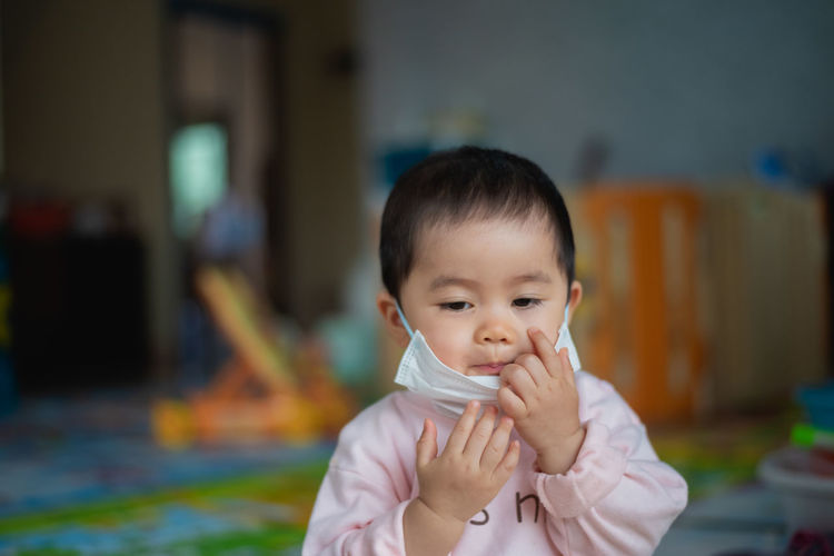 Cute baby girl wearing mask at home