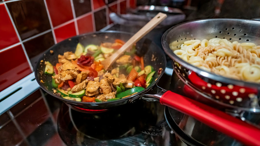 Close up and selective focus of a spicy chicken dish cooking in a non-stick wok on the oven hob