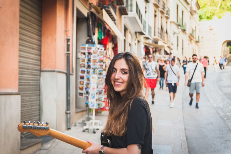 Portrait of young woman playing guitar while standing on sidewalk in city