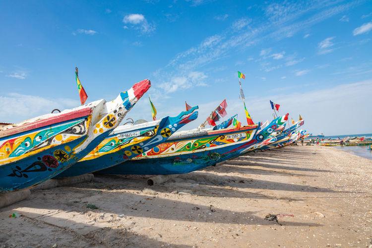 Fishing boat on beach against blue sky