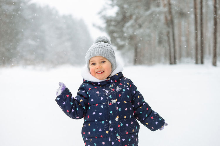 Portrait of cute little girl having fun playing outdoor during snowfall.