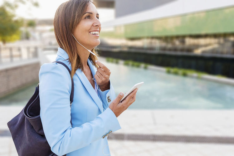 Side view of a smiling woman in blue jacket holding mobile while listening music with earphones Technology Connection Wireless Technology One Person Communication Young Adult Businesswoman Adult Women Standing Business Person Portable Information Device Young Women Architecture City Smart Phone Smiling Day Telephone Beautiful Woman Outdoors