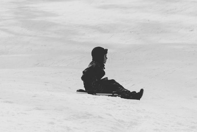 Side view of boy tobogganing on snow