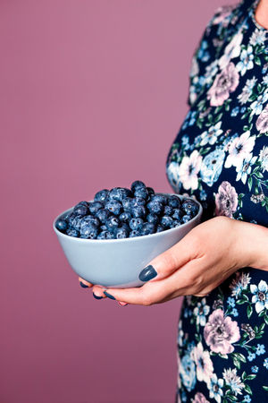 Close shot of female hands holding bowl filled with fresh blueberries. Woman wearing flowery blue dress standing at front of purple background. Side view, vertical shot. Berries Dessert Eating Freshness Life Woman Young Berry Blueberries Blueberry Enjoying Enjoyment Female Food Fresh Fruit Garden Girl Healthy Joy Organic Outdoors person Summer Sweet
