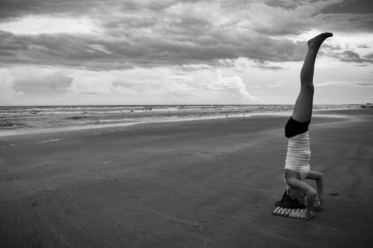 Side view of woman practicing sirsasana at beach against sky