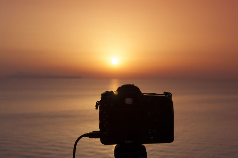 Close-up of camera on sea against sky during sunset