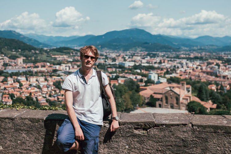 Portrait of young man wearing sunglasses standing by retaining wall against townscape