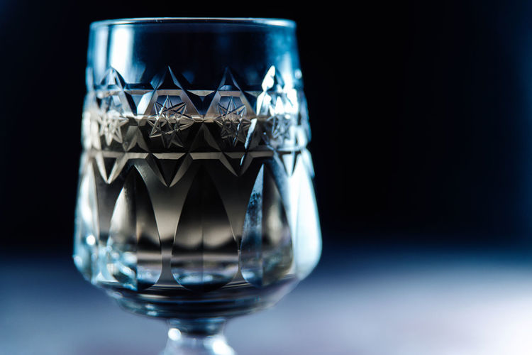 Close-up of glass on table against black background