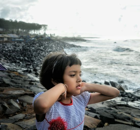Thoughtful girl at rocky coastline against sky
