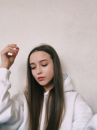 Beautiful young woman with eyes closed against wall