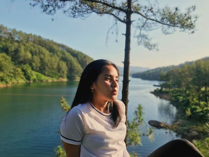 Woman looking away while sitting by lake against mountain and sky