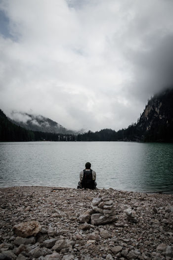 Rear view of man sitting on rock by lake against sky