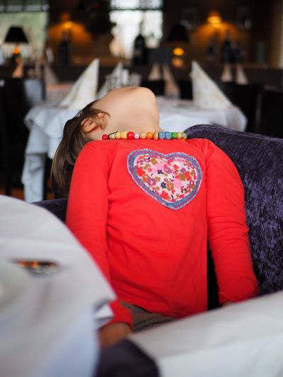 Real People One Person Indoors  Selective Focus Lifestyles Women Red Relaxation Incidental People Leisure Activity Furniture Child Childhood Portrait Girls Human Body Part Emotion Innocence Looking Up Restaurant Red Red Color Heart Perspective Bored Boredom Necklace Waiting