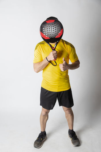 Low section of man standing against yellow background