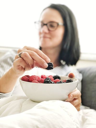 Mature woman eating fruits while sitting on sofa at home