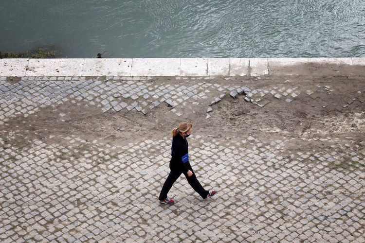 High angle view of woman walking on footpath by sea