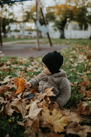 Rear view of boy on dry leaves on field