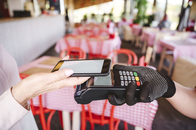 Midsection of man using mobile phone in restaurant