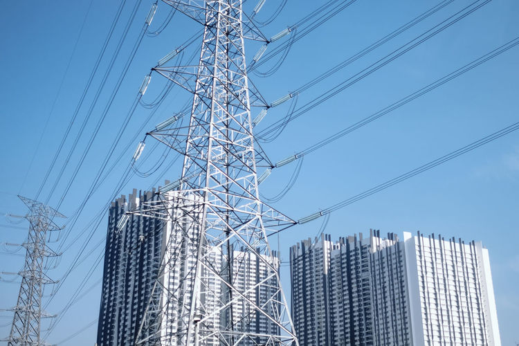 Low angle view of electricity pylon and buildings against sky