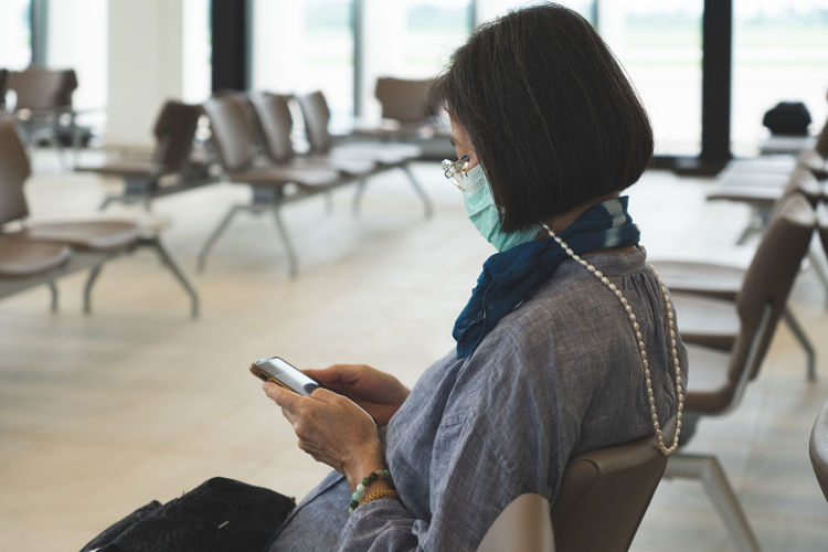 Woman wearing mask using mobile phone while sitting on chair