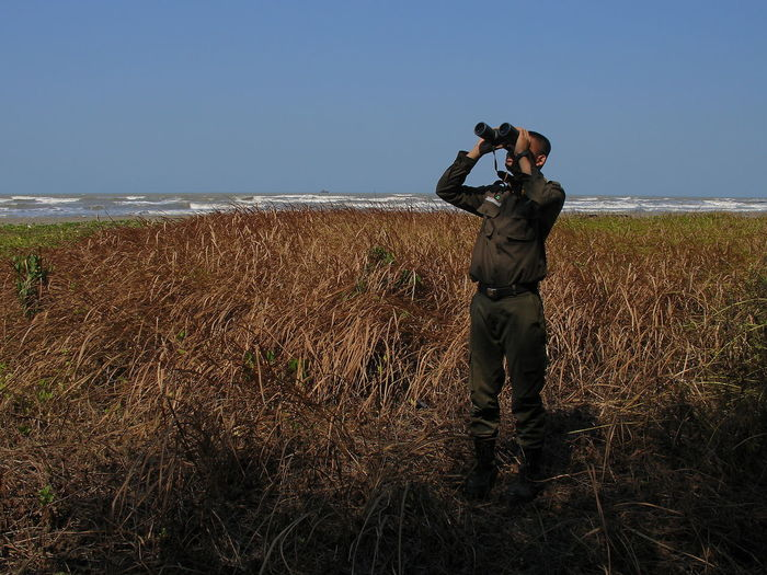Full length of man photographing on sea against clear sky