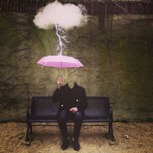 Decapitated man sitting under pink umbrella
