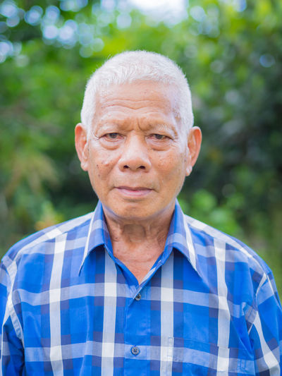 A portrait of an elderly man looking at the camera while standing in a garden.