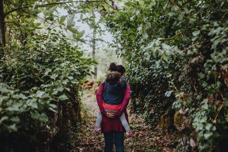 Rear view of woman standing amidst plants in forest