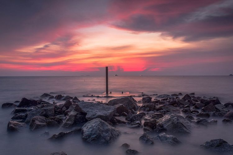 beach scenery during sunset Beach Beauty In Nature Cloud - Sky Groyne Horizon Horizon Over Water Idyllic Land Nature No People Orange Color Outdoors Rock Rock - Object Rocky Coastline Scenics - Nature Sea Sky Solid Sunset Tranquil Scene Tranquility Water
