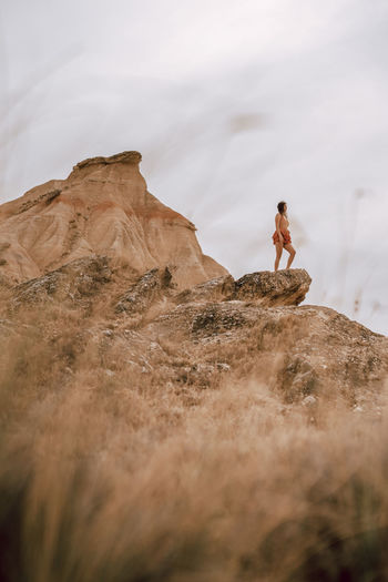 Low angle view of woman standing on mountain