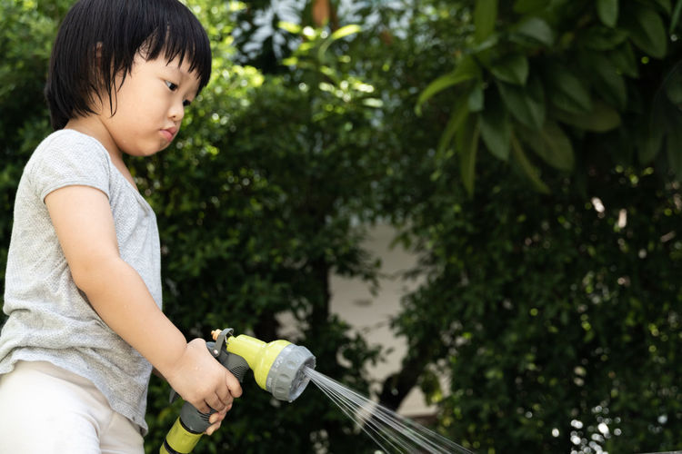 Funny moment of 3 year old asian kid playing water with garden hose in backyard. background concept