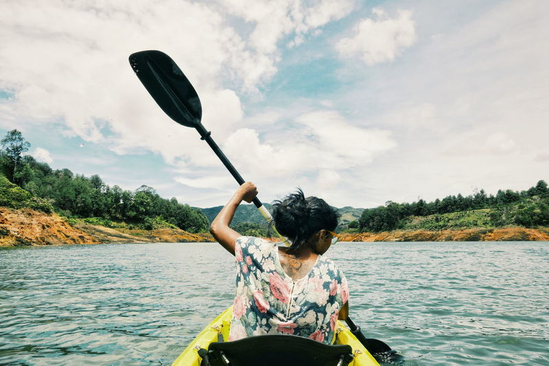 Rear view of woman kayaking on lake against sky