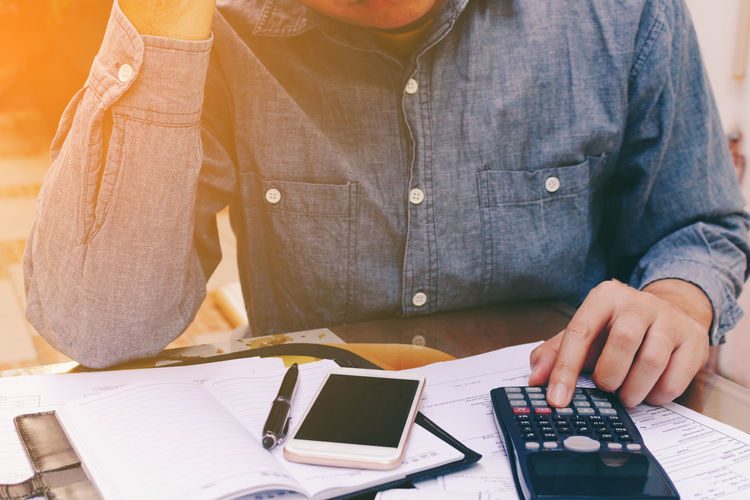 Midsection Of Man With Calculating On Desk At Office