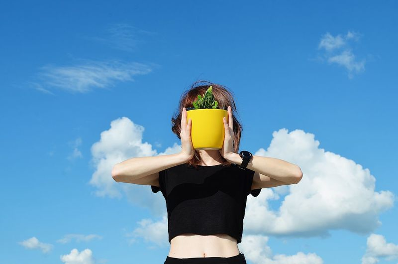Woman Covering Face With Potted Plant Against Blue Sky