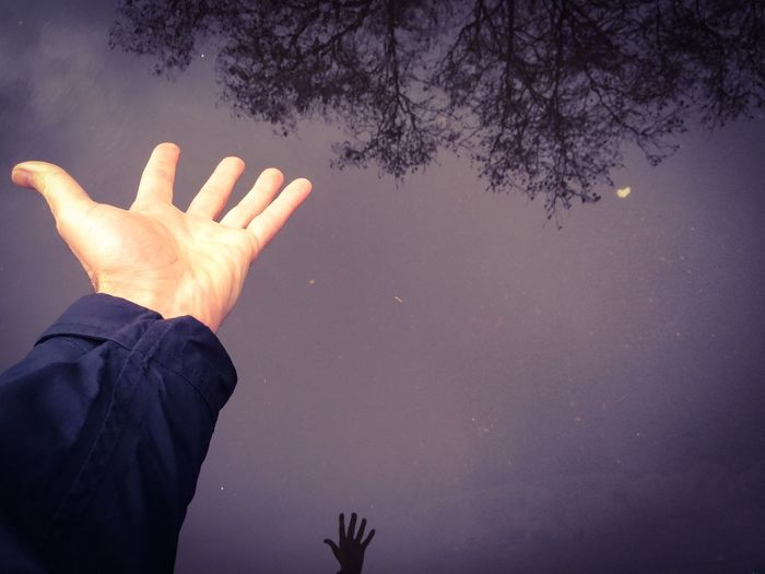 Cropped hand over lake