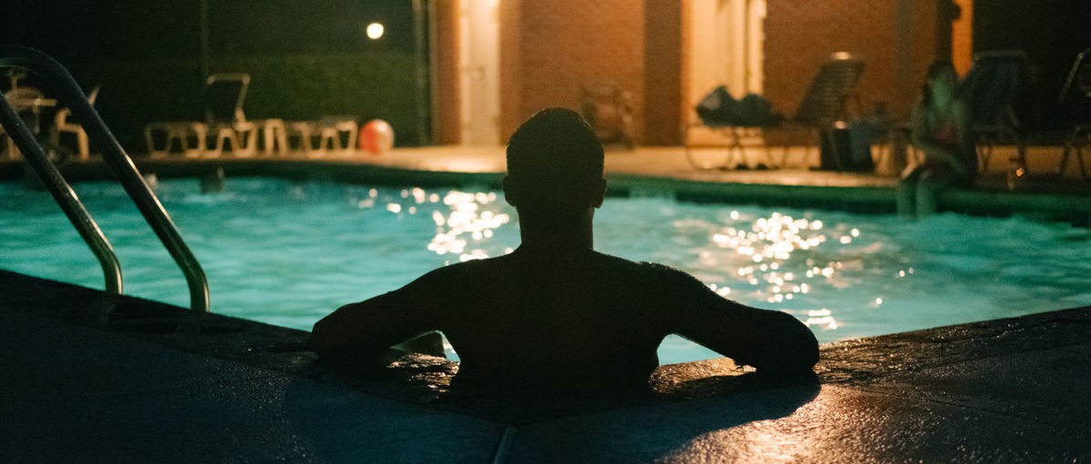 Rear view of man in swimming pool