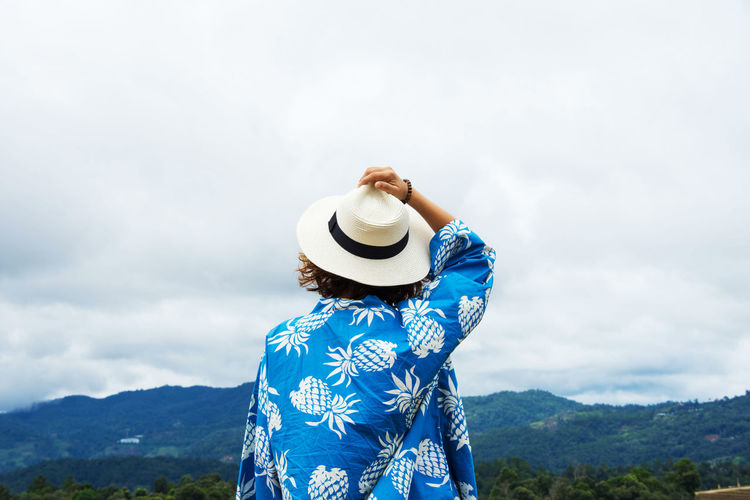 Beauty In Nature Cloud - Sky Day Hat Leisure Activity Mountain Mountain Range Nature One Person Outdoors People Real People Scenics Sky Standing Sun Hat Tree Vacations Women