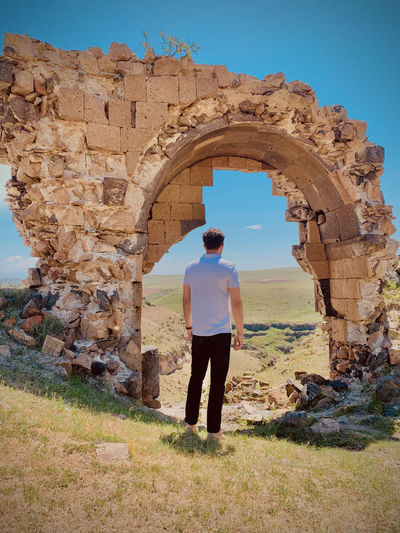 Rear view of man standing against old ruins