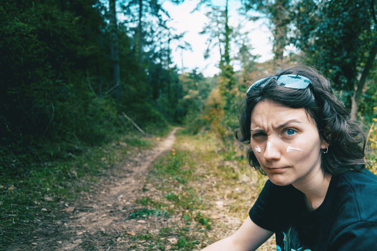 Portrait of a blue-eyed girl looking at camera and making fun with sunscreen on her face in nature