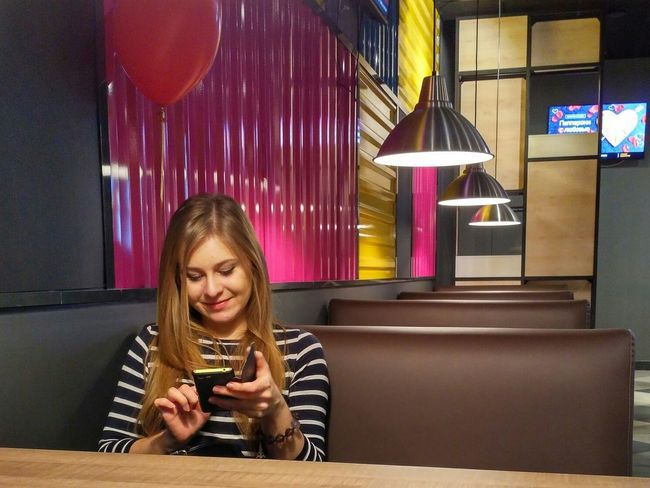 Mobile Conversations One Girl Only Portrait Girls Blond Hair One Person Front View Smiling Chating With Friend Intouch Cafe People Mobile Conversations