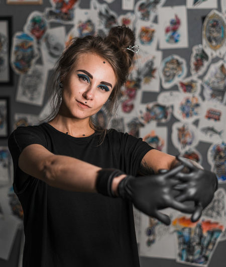 Piercing master, portrait Looking At Camera Indoors  One Person Young Adult Portrait Front View Casual Clothing Real People Standing Young Women Wall - Building Feature Waist Up Art And Craft Lifestyles Creativity Leisure Activity Focus On Foreground Home Interior Hairstyle