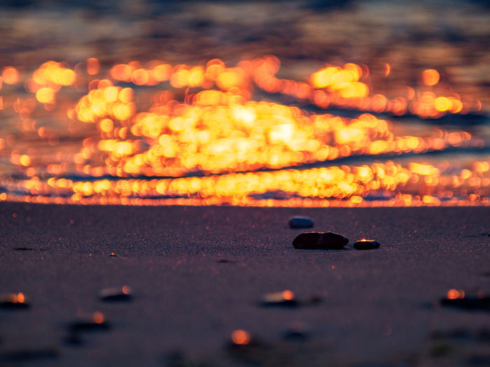 Surface level of illuminated fire against sky at sunset