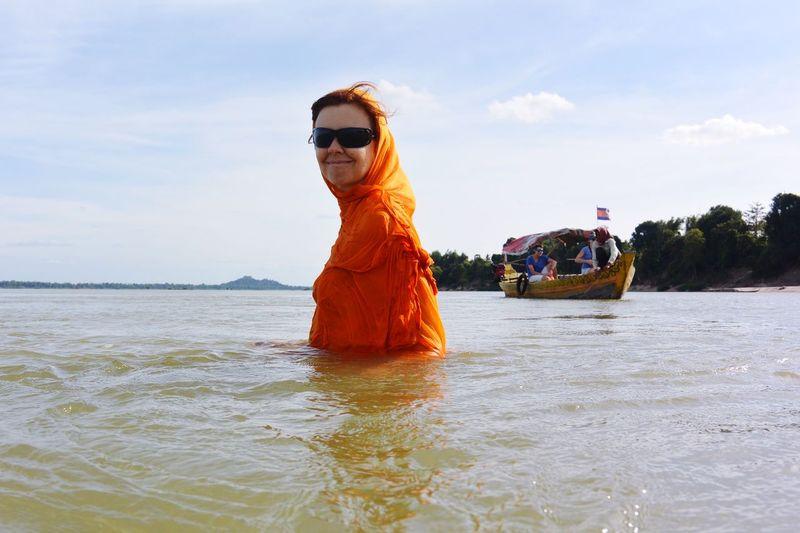 Woman wearing sunglasses on sea against sky