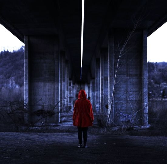 Rear view of woman wearing red hood while standing below bridge