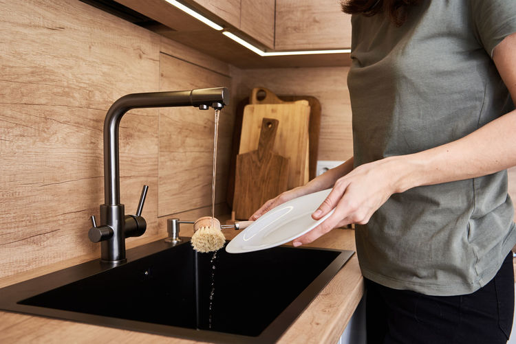 Woman washes dishes with wooden eco friendly brush. zero waste concept